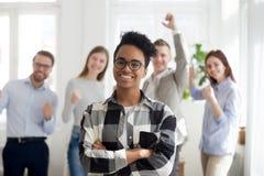 Lyckliga anställda som står på kontoret som ser kameran arkivbilder