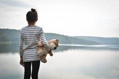 Lyckliga asiatiska barn med nallebjörnen i natur, kopplar av tid på ferie Fotografering för Bildbyråer