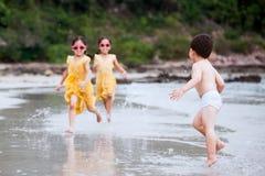 Lyckliga asiatiska barn som har gyckel som spelar, och körning på stranden Royaltyfria Foton
