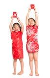 Lyckliga asiatiska barn som rymmer det röda paketet Royaltyfri Bild