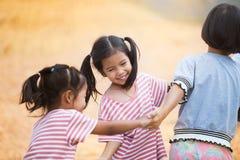 Lyckliga asiatiska barn som rymmer handen och gör cirkeln Arkivfoto