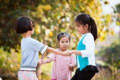 Lyckliga asiatiska barn som rymmer handen och gör cirkeln Arkivfoton