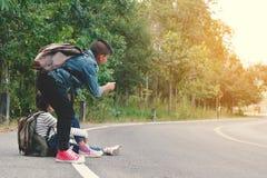 Lyckliga asiatiska barn vandrar i väg- och skogbakgrunden arkivfoton