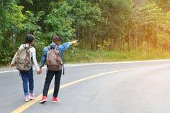 Lyckliga asiatiska barn vandrar i väg- och skogbakgrunden royaltyfri bild