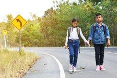Lyckliga asiatiska barn vandrar i väg- och skogbakgrunden royaltyfri foto