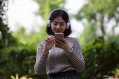 Lyckliga asiatiska flickor lyssnar till musik royaltyfri foto