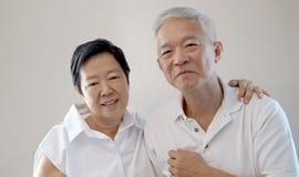 Lyckliga asiatiska höga par på vit bakgrund älskar och kramar Royaltyfria Bilder