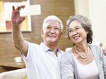 Lyckliga asiatiska höga par som tar en selfie fotografering för bildbyråer