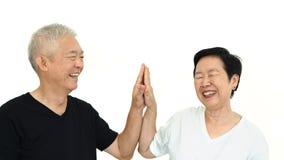 Lyckliga asiatiska höga parinnehavhänder på den vita isolatbackgroen Royaltyfri Foto