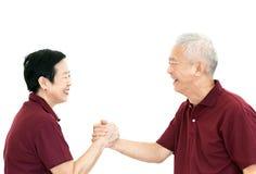 Lyckliga asiatiska höga parinnehavhänder på den vita isolatbackgroen Royaltyfria Foton
