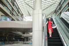 Lyckliga asiatiska kinesiska moderna shoppingpåsar för trendig kvinna i elevator för hiss för skratt för leende för köpare för so arkivfoto