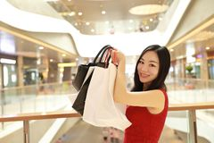 Lyckliga asiatiska kinesiska moderna shoppingpåsar för trendig kvinna i förbrukning för skratt för leende för köpare för galleria arkivfoto