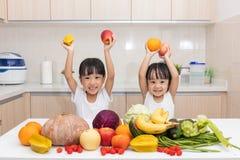 Lyckliga asiatiska kinesiska små systrar med frukt och grönsaken Arkivfoto