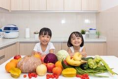 Lyckliga asiatiska kinesiska små systrar med frukt och grönsaken Royaltyfri Foto