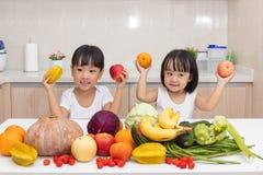Lyckliga asiatiska kinesiska små systrar med frukt och grönsaken Fotografering för Bildbyråer