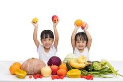 Lyckliga asiatiska kinesiska små systrar med frukt och grönsaken Arkivfoton