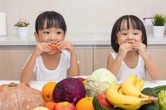 Lyckliga asiatiska kinesiska små systrar som äter frukt och grönsaken Royaltyfri Foto