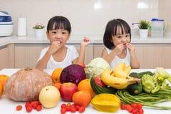 Lyckliga asiatiska kinesiska små systrar som äter frukt och grönsaken Arkivfoto