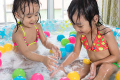 Lyckliga asiatiska kinesiska små systrar som spelar i det uppblåsbara bajset Arkivfoto