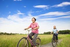 Lyckliga asiatiska äldre pensionärer kopplar ihop att cykla i lantgård Arkivfoto
