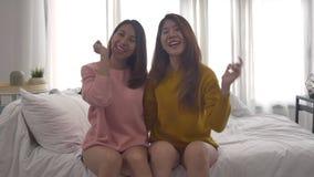 Lyckliga asiatiska lesbiska lgbtpar tycker om underhållning i vardagsrum Härliga kvinnor som ligger på en soffa, lyssnar till mus lager videofilmer