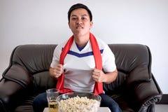 Lyckliga asiatiska män som håller ögonen på fotbollsmatchen på tv och att hurra som är footbal arkivfoto