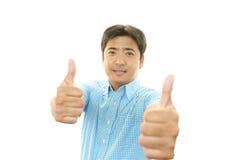 Lyckliga asiatiska manvisningtummar up tecknet royaltyfria foton