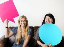 Lyckliga asiatiska och Caucasian kvinnavänner som rymmer copyspaceanförande, bubblar arkivbilder