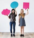 Lyckliga asiatiska och Caucasian kvinnavänner som rymmer copyspaceanförande, bubblar royaltyfria foton