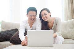 Lyckliga asiatiska par genom att använda bärbar dator Arkivbild
