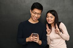 Lyckliga asiatiska par som tillsammans står och använder smartphonen Fotografering för Bildbyråer