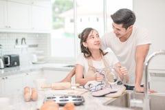 Lyckliga asiatiska par som tvättar disken efter frukosten, mål arkivfoton