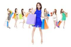 Lyckliga asiatiska shoppingkvinnor som rymmer färgpåsar royaltyfri foto