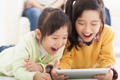 Lyckliga asiatiska små flickor som använder minnestavlan Arkivfoto