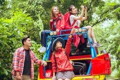 Lyckliga asiatiska unga handelsresande med 4WD kör bilen av vägen i skog Royaltyfri Bild
