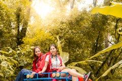 Lyckliga asiatiska unga handelsresande med 4WD kör bilen av vägen i skog Royaltyfri Fotografi