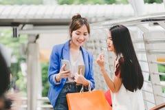 Lyckliga Asien kvinnor med smarta telefon- och shoppingpåsar Royaltyfria Foton