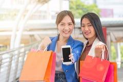 Lyckliga Asien kvinnor med smarta telefon- och shoppingpåsar Royaltyfria Bilder