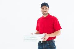 Lyckliga askar för pizza för leveransman hållande Royaltyfria Bilder