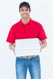 Lyckliga askar för pizza för leveransman hållande Royaltyfri Fotografi