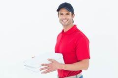 Lyckliga askar för pizza för leveransman hållande Arkivbilder