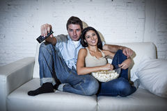 Lyckliga attraktiva par som har rolig hemmastadd tyckande om hållande ögonen på television att kopplas av Arkivbild
