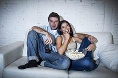 Lyckliga attraktiva par som har rolig hemmastadd tyckande om hållande ögonen på television att kopplas av Arkivbilder