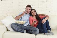 Lyckliga attraktiva par som har rolig hemmastadd tyckande om hållande ögonen på televisionfilm Royaltyfri Foto