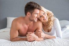 Lyckliga attraktiva par som kopplar av på deras säng Royaltyfria Bilder