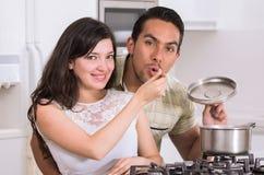Lyckliga attraktiva par som tillsammans lagar mat royaltyfria foton