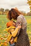 Lyckliga Autumn Family Den gulliga modern och sonen som kramar i nedgång, parkerar royaltyfri foto