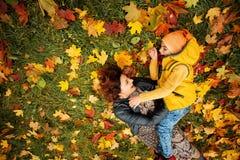 Lyckliga Autumn Family i nedgång parkerar utomhus- arkivbilder