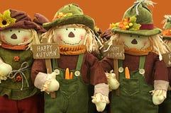Lyckliga Autumn Is Wished vid rad av fågelskrämmor Royaltyfria Bilder
