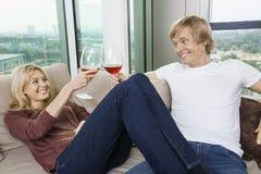 Lyckliga avkopplade par som hemma rostar vinexponeringsglas i vardagsrum Royaltyfri Fotografi